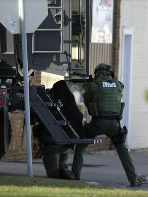 Police officers use an armored truck for cover during the Dec. 5, 2015, standoff at Eagle Nation Cycles in Neenah, Wis.