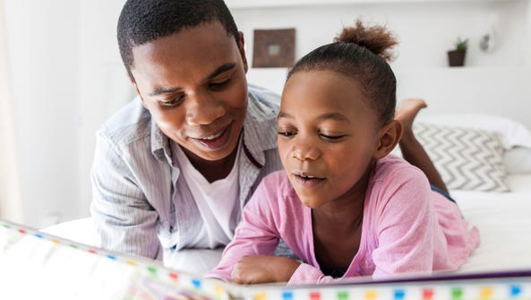 A father listening to his daughter read.