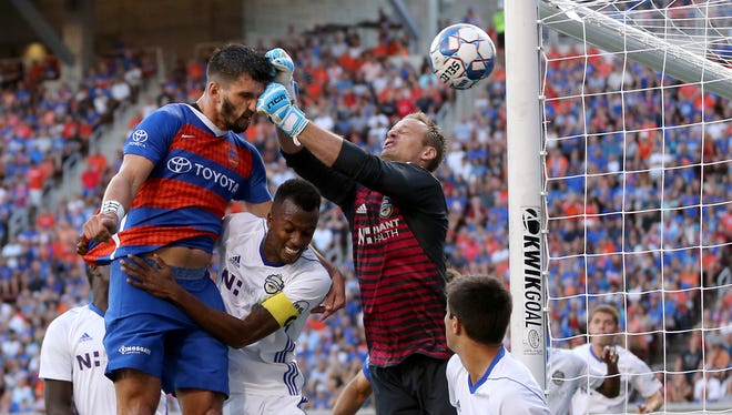 FC Cincinnati defender Forrest Lasso (3) is punched in the face by Charlotte Independence goalkeeper Andrew Dykstra (50) on an attempt on goal in the first half of a USL match between Charlotte Independence and FC Cincinnati, Wednesday, July 18, 2018, at Nippert Stadium in Cincinnati.