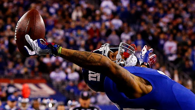 Odell Beckham of the New York Giants makes a one-handed catch against the Dallas Cowboys on Nov. 23, 2014 in East Rutherford, New Jersey.