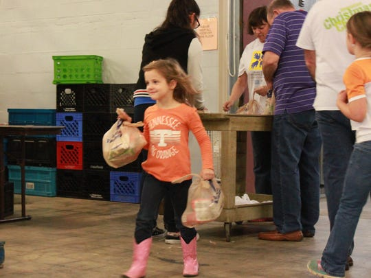 Madelyn Haynes, 5, helps carry bags of food Saturday at the Regional Inter-Faith Association. Saturday was Make A Difference Day, the nation's largest day of community service