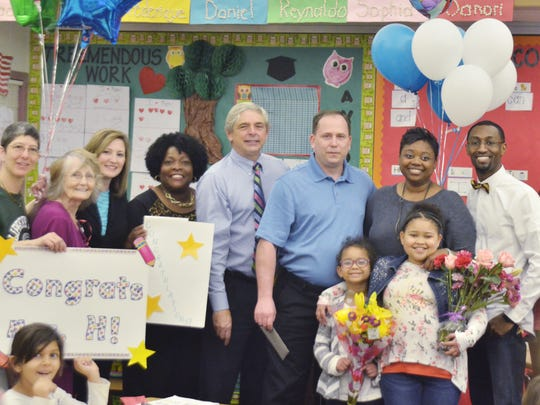 Springwood Elementary teacher Cloris Mobley-Hajdukiewicz,second right, won the 2016 Glenn-Howell Distinguished Educator of the Yearaward. She was described as a dedicated and caring teacher who goes aboive and beyond to help her students. Here, Mobley-Hajdukiewicz poses for a photo with her husband, Rich, third right, daughters, Olivia, 7, left of her, and Nia, 9, and fellow educators.