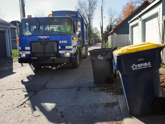 Jason Turner with Republic Services empties recycling cans in an alley at 13th and Ogden Streets in Indianapolis on Friday, November 2, 2012. (Matt Detrich / The Star)