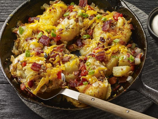 Smashed potatoes loaded with vegetables, cheddar and applewood-smoked bacon are cooked in a cast-iron skillet on the grill.