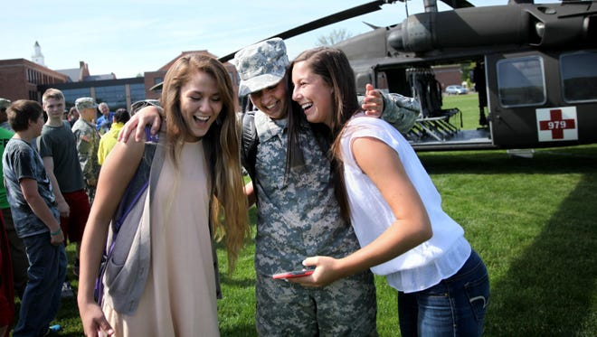 Kesyanda Trader (center), a student at Menasha High School who will be going into the National Guard, laughs with her friends, Alli Carrillo (left) and Kayla Kuranda, after taking a selfie in front of a Black Hawk helicopter. Trader and other local students who will be joining the National Guard flew into Menasha on May 20 aboard the military helicopter. The helicopter flight from West Bend was the first flight Trader has ever taken.