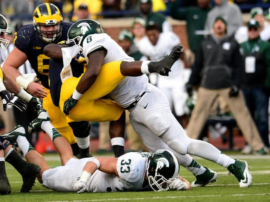 Michigan State's Lawrence Thomas upends Michigan running back De'Veon Smith near the line of scrimmage in the third quarter of the Spartans 27-23 victory Saturday in Ann Arbor. MSU held the Wolverines' running backs to 87 yards on 29 attempts.
