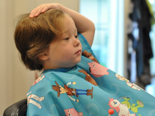 Reagan Sweat checks out his first haircut. The 4-year-old was able to donate 12 inches of hair to the nonprofit Wigs For Kids.