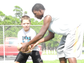 A volunteer instructs a camper during quarterback drills at Mike Cadore's 'I Got Skillz' football camp in Rockledge, partnered with USA Football and the NFL.