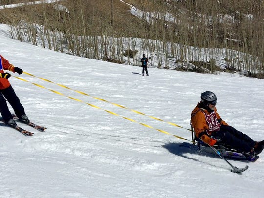 A disabled veteran uses adaptive equipment to ski the slopes of Snowmass near Aspen, Colo.