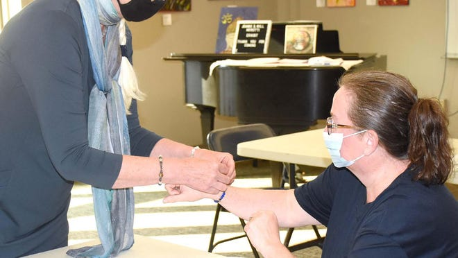 Sharon Collins (left) ties a bracelet around Carol Whritenour's wrist after sizing it for her at Friday's Little Falls Public Library class.