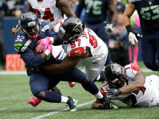 Seattle Seahawks running back Christine Michael (32) is tackled by Atlanta Falcons defensive tackle Grady Jarrett (97) in the first half of Sunday's game in Seattle.