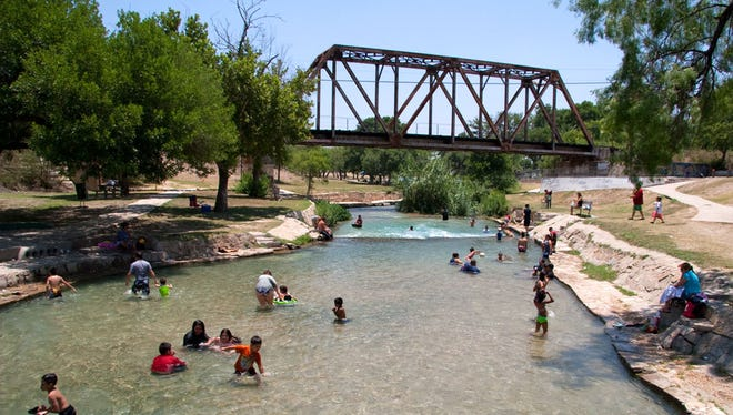 Del Rio residents are seen playing in the water at Moore Park as summer temperatures climb in West Texas.