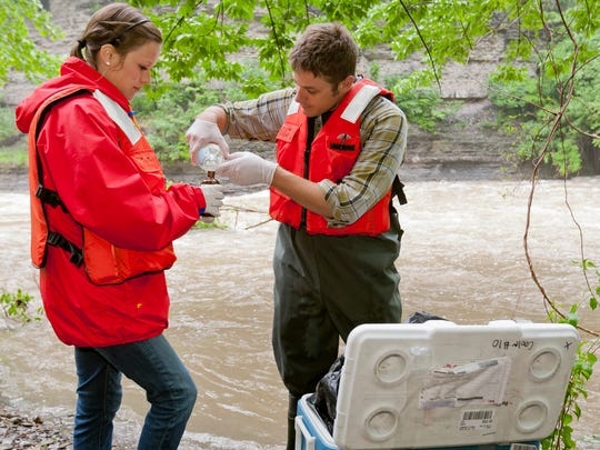Hydrologic Technicians Shannon Garvin, of Orwell, and Brett Hayhurst of Enfield distribute water samples taken Monday from Fall Creek near the Lake Street bridge in Ithaca. The samples are part of a national survey looking at the distribution and effects of multiple chemicals in waterways.