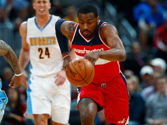 Washington Wizards guard John Wall, front, picks up a loose ball in front of Denver Nuggets center Mason Plumlee during the first half of an NBA basketball game Wednesday, March 8, 2017, in Denver. (AP Photo/David Zalubowski)
