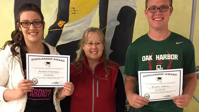 Civilian Marksmanship Program staff member Michelle Woods, center, awarded two local scholarship winners, Kaitlyn Fourman and Brayden Jeffries, both members of a local 4-H air rifle program.