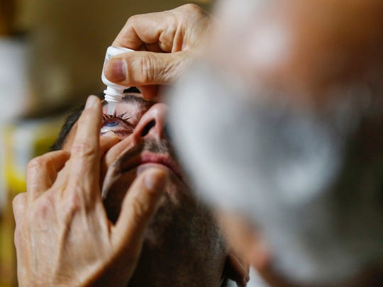 Niazi Altuhafi puts drops in Yousif Khalaf Shaheen's eye on Wednesday, Jan. 10, 2018. Yousif is a Yazidi fighter who was wounded by ISIS and is staying with Niazi and his family while he gets treatment for his damaged eye.