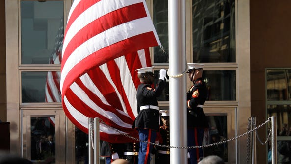 People watch the U.S. flag as it is raised during a