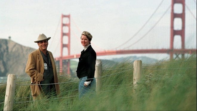 In this March 30, 1998, file photo, Larry Harvey, left, and Marian Goodell, two of the founders of the Burning Man festival walk near Baker Beach in San Francisco with the Golden Gate Bridge in the background.