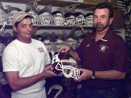 Tim Sparkman (right) and former Astronaut football coach Randy Hallock check out helmets before 2002 spring practice.