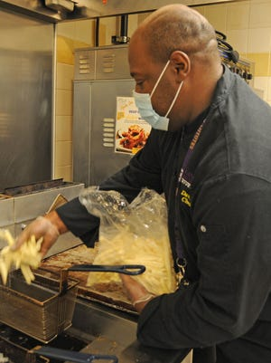 Vincent Davis, executive chef with Sodexo, puts french fries in the frying basket inside the Student Activities Center at Kansas Wesleyan University.