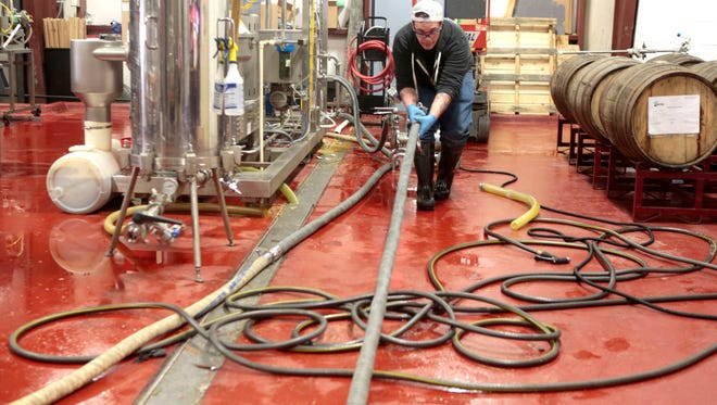 Brewer Zack Wanner with MadTree Brewing pulls hoses to a mobile pump on Thursday. Co-founder Kenny McNutt said MadTree uses a centrifuge to pull solid materials out of their waste before it goes down the drain, and that their waste is mostly comprised of organic materials like yeast and occasionally caustics used for cleaning. MadTree could be forced to pay a surcharge for the materials they pour into the wastewater system.