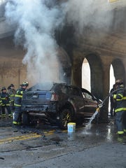 Indianapolis fire crews douse flames in a car after it struck a bridge support in the 900 block of South Emerson Avenue on Tuesday.