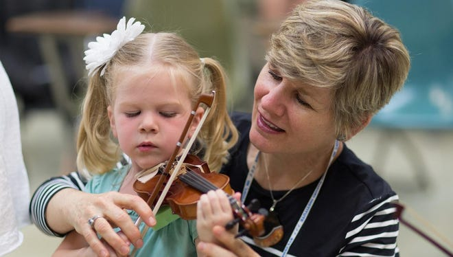 Stephanie Price, of Champaign, Illinois, helps her granddaughter Elise, 4, with violin technique at the American Suzuki Institute in July, held at the University of Wisconsin.