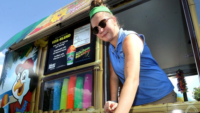 Lauren Woods hands Andrew Price, 8, a root beer float Kona Ice from the mobile truck near the Splash Pad at Gregory Mill Park in Smyrna on Monday.