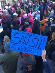 "A man holds up a ""smash the patriarchy,"" sign at a"