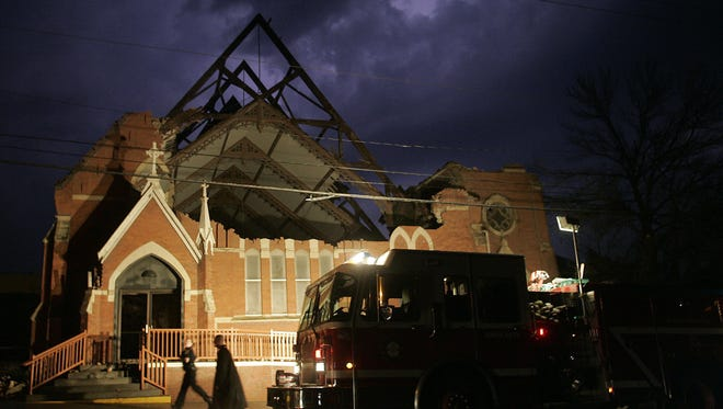 Iowa City firefighters inspect St. Patrick's Catholic Church in Iowa City after an F2 tornado ripped the roof off on April 13, 2006.