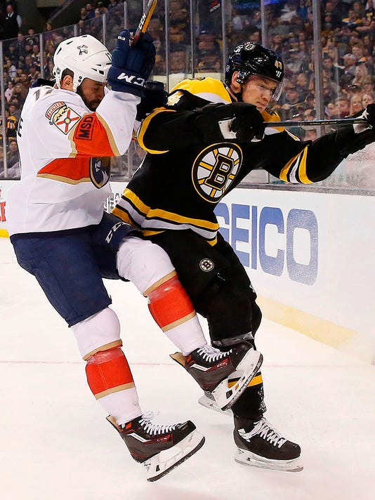 Florida Panthers' Derek MacKenzie, left, checks Boston Bruins' Nick Holden (44) during the first period of an NHL hockey game in Boston, Saturday, March 31, 2018. (AP Photo/Michael Dwyer)