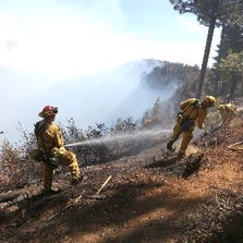 Firefighters hose down hot spots of the King Fire near Pollack Pines, Calif., Monday, Sept. 15, 2014. The fire, which started Sunday has consumed more than 3,000 acres and forced the evacuation of dozens of homes.