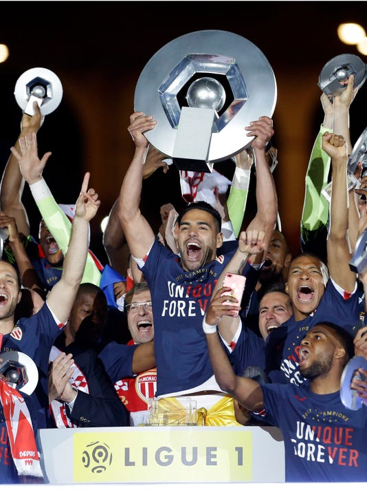 Monaco players hold the trophy as they celebrate their French League One title after beating Saint Etienne during the League One soccer match Monaco against Saint Etienne, at the Louis II stadium in Monaco, Wednesday, May 17, 2017. Monaco clinched its first league title since 2000 and eighth overall, replacing Paris Saint-Germain as champion. (AP Photo/Claude Paris)