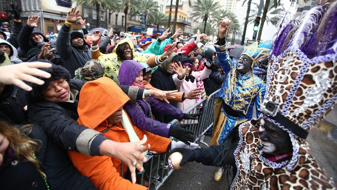 Participants of the Krewe of Zulu Parade hand out painted coconuts to spectators in New Orleans on  March 4, 2014.