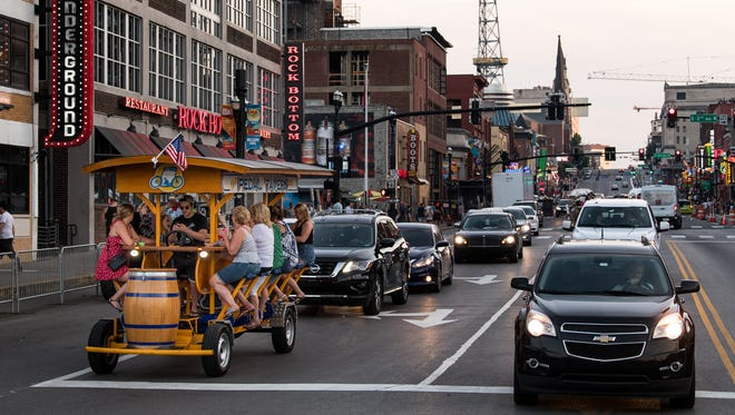 A pedal tavern is surrounded by cars as they wait for a light to turn green on Broadway in Nashville, Tenn., Thursday, May 24, 2018.