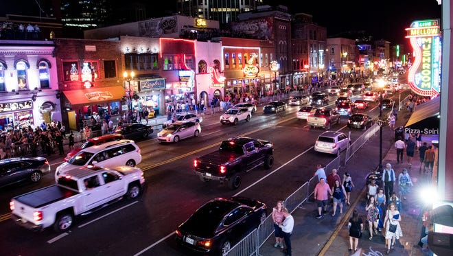 Traffic passes down Broadway in Nashville on Thursday, May 24, 2018. Broadway in recent years has attracted major corporate investment anddoled out lucrative licensing deals to country stars such as Blake Shelton and Dierks Bentley to open name-branded bars.