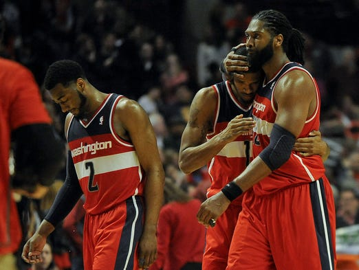 Game 5 in Chicago -- Wizards 75, Bulls 69: Washington Wizards forward Nene Hilario, right, celebrates with guard John Wall, left, and forward Trevor Ariza (1) after defeating the Chicago Bulls.
