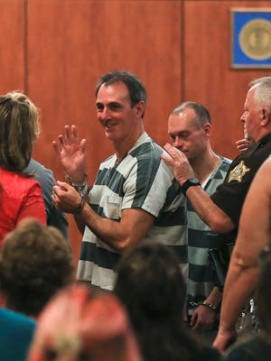 Jeffrey Dewayne Clark waves to family members as fellow inmate Garr Keith Hardin walks behind them after the pair is escorted out of the Meade Circuit Court Thursday morning. Meade Circuit Judge Bruce T. Butler says he needs time to consider bail for the two Kentucky men whose conviction for a supposedly Satanic-inspired murder was vacated.
