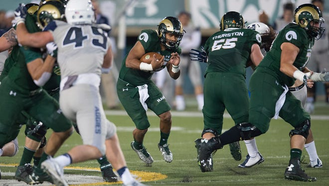 CSU running back Izzy Matthews finds an opening in Aggies defense during a game against Utah State at Hughes Stadium Saturday, October 8, 2016.