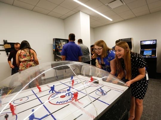 Haley King of Auburn Hills, left and Savanna Trottier of Lapeer play dome hockey in the game room at United Shore's new headquarters in Pontiac, Mich. on Wednesday, June 20, 2018.