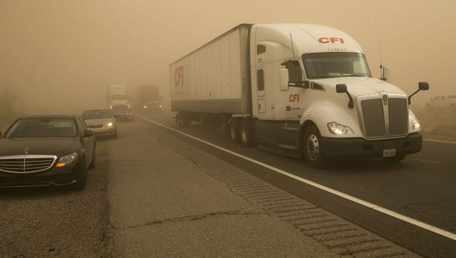 Some vehicles pull over as others drive through a dust storm on I-10, southeast of Riggs Road on the Gila River Indian Community on Monday afternoon, February 19, 2018.