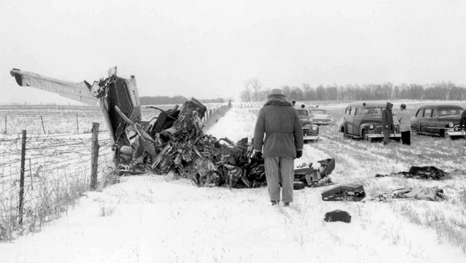 """Officials survey the wreckage on Feb. 3, 1959, of a plane that was carrying musicians Buddy Holly, Ritchie Valens, J.P. """"Big Bopper"""" Richardson and pilot Roger Peterson. The crash killed all on board."""
