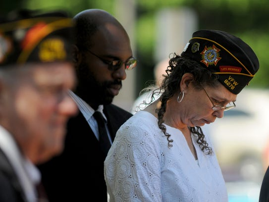 Members of the VFW bow their heads as names of fallen