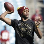 FILE - In this Nov. 22, 2015, file photo, Washington Redskins' Robert Griffin III warms up before an NFL football game against the Carolina Panthers in Charlotte, N.C. Two people familiar with the situation say that free-agent quarterback Robert Griffin III is visiting with the New York Jets on Friday, March 11, 2016. Griffin was cut by the Washington Redskins on Monday, ending a tumultuous tenure in which he immediately became a star in 2012 before eventually spending all last season on the sideline because of injuries and inconsistency. The people spoke to The Associated Press on condition of anonymity because the team does not announce player visits. (AP Photo/Bob Leverone, FIle)