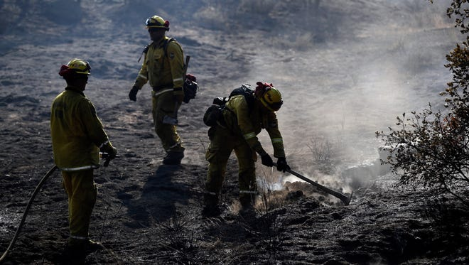 Firefighters hose down hot spots along Highway 243 on Thursday, July 26, 2018, near Idyllwild, Calif. A fast-moving wildfire tore through trees, burned several homes and forced evacuation orders for an entire mountain town as California sweltered under a heat wave and battled ferocious fires at both ends of the state.
