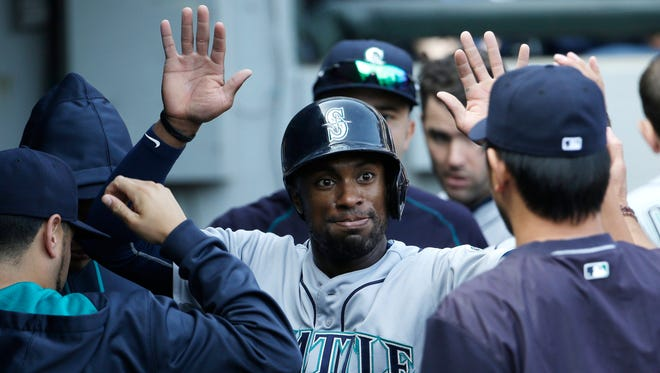 Seattle Mariners' Austin Jackson celebrates with teammates after scoring on a single by Kyle Seager during the eighth inning of a baseball game against the Chicago White Sox, Sunday, Aug. 30, 2015, in Chicago.