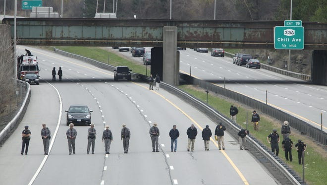 State Troopers and police officers search for evidence after a truck was reportedly shot at on I-390 in Gates.
