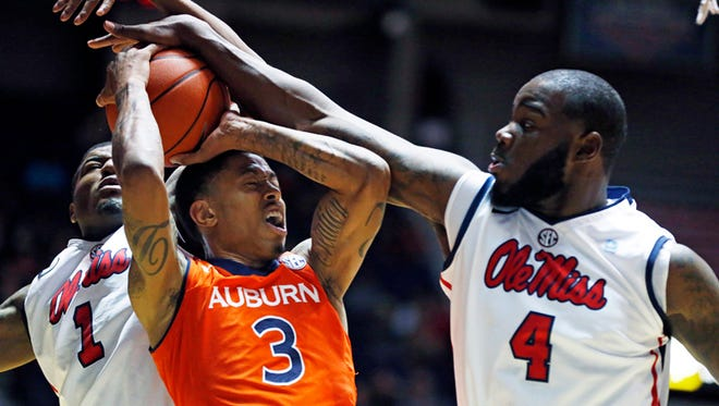 Mississippi center Demarco Cox (4) and guard Martavious Newby (1) block Auburn guard Chris Denson (3) as he attempts a layup in the first half of an NCAA college basketball game in Oxford, Miss., Thursday, Jan. 9, 2014. Mississippi won 65-62. (AP Photo/Rogelio V. Solis)