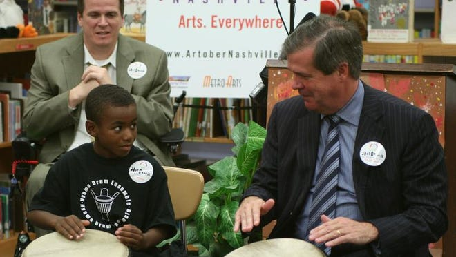 A Tulip Grove Elementary student teaches Mayor Karl Dean how to play an African drum at the Artober Nashville launch in 2014.