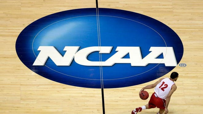 In this March 26, 2014, file photo, Wisconsin's Traevon Jackson dribbles past the NCAA logo during practice at the NCAA men's college basketball tournament in Anaheim, Calif. A federal judge ruled that the NCAA can't stop players from selling the rights to their names, images and likenesses, striking down NCAA regulations that prohibit them from getting anything other than scholarships and the cost of attendance at schools. U.S. District Judge Claudia Wilken in Oakland, Calif., ruled in favor Friday, Aug. 8, of former UCLA basketball star Ed O'Bannon and 19 others in a lawsuit that challenged the NCAA's regulation of college athletics on antitrust grounds.